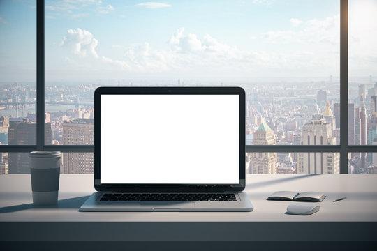 Modern desk with empty white laptop