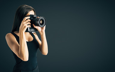 Woman taking photo on black background