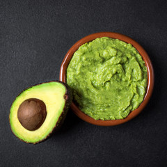 Traditional Mexican Dip Sauce Guacamole in a bowl with cutted in a  half avocado  on black background. Top view