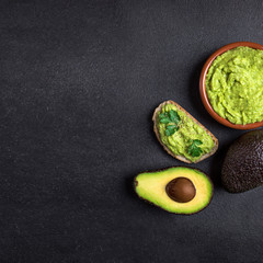 Traditional Mexican Dip Sauce Guacamole in a bowl with bread toasts,  whole and cut half avocado  on dark background. Top view. Copy space.