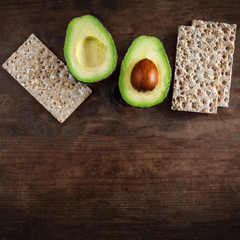 Avocado fruit. Two halves of avocado with wholegrain crispy bread  slices on brown wooden  background.  Copyspace. Top view.