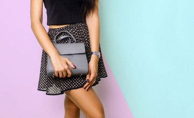 Close up of gray leather handbag in hand of stylish woman, studio shot on gray background. Female fashion and accessories. Wall mural