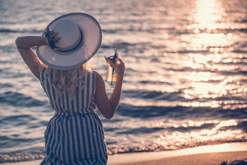 Foto op Plexiglas Art Studio Girl wearing striped dress walking standing and holding a hat and a cocktail on the sea shore. Marine clothing style.