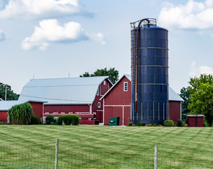 Modern, bright red barn, farm buildings and blue silo, with blue sky and puffy clouds. Working family farm with beautiful barns and lawn