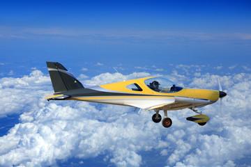 Piękny żółty samolot, awionetka nad chmurami.