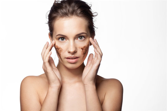 Portrait of sensual girl using cleansing cosmetology peeling on white background. Beautiful female with natural coffee mask. Perfect fresh clean skin concept.