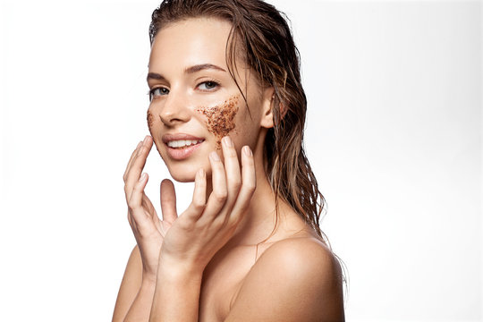 Portrait of happy girl with beauty scrub on face on white background. Sensual female applying natural coffee mask for exfoliating and moistening. Perfect fresh clean skin concept.