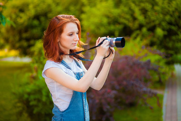 Red-haired girl with a camera taking pictures in the Park