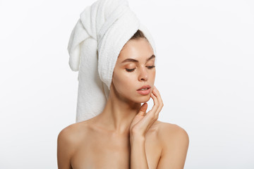 Spa and beauty concept - happy young girl with clean skin and with a white towel on her head washes face
