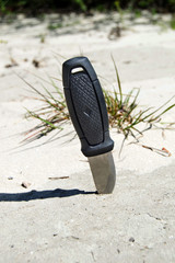 The hunting knife with a black handle is stuck in the sand