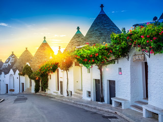 Traditional Trulli houses in Alberobello village, illuminated at sunrise in Bari region of Italy.