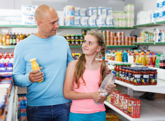 Preteen girl with father holding different  goods in supermarket