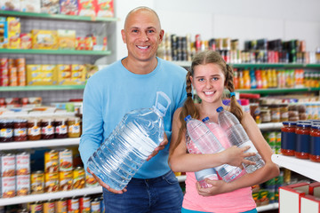 family of smiling father and tween daughter buying still water in supermarket