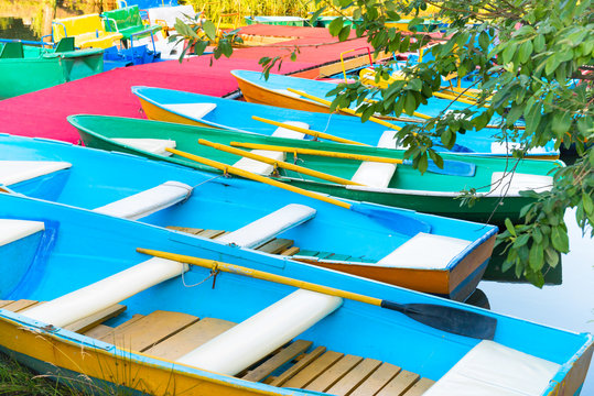 Row of many empty colorful boats at pier