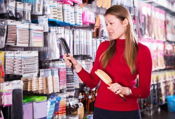 Female choosing hair combs in store