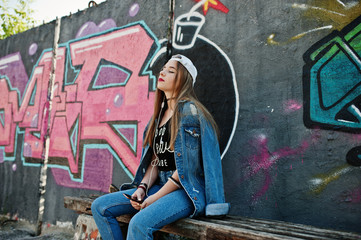Stylish casual hipster girl in cap and jeans wear listening music from headphones of mobile phone against large graffiti wall with bomb.