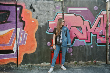 Stylish casual hipster girl in jeans wear and glasses against large graffiti wall.