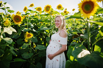 Blonde pregnant mother in sunflowers field. Happy moments of pregnancy.
