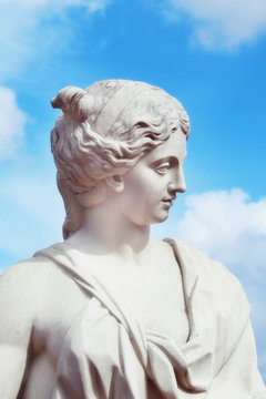 Sculpture of woman of white material against blue sky with white
