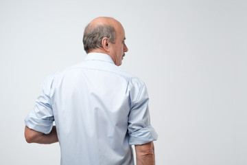 Back view of senior bald caucasiant man in casual shirt