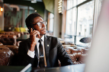 Business african american man wear on black suit and glasses sitting at office and speaking on phone behind laptop.