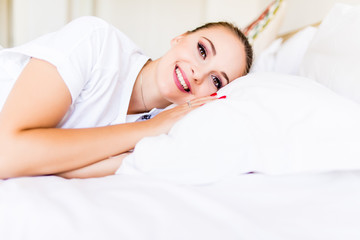 Young woman wake up with smile relaxing in bed during the morning