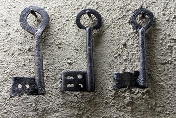 Three vintage black keys on white wall