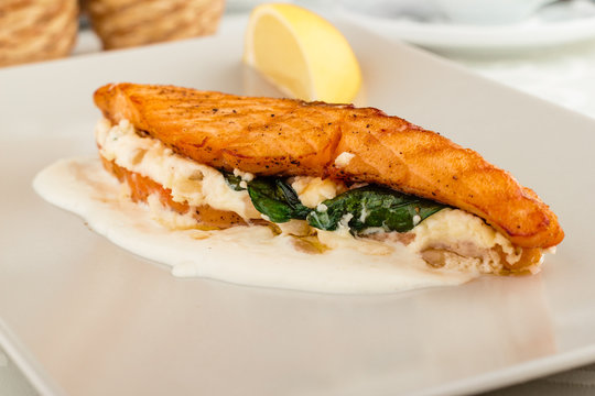 A baked stuffed salmon with lemon on the side