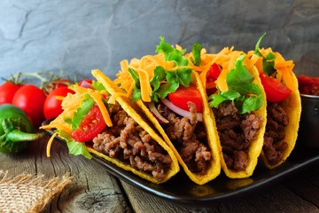 Traditional hard shelled tacos with ground beef, lettuce, tomatoes and cheese. Scene with a dark background.