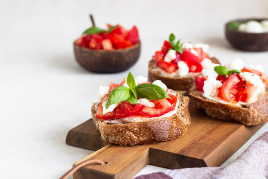 Italian bruschetta with chopped cherry tomatoes, mozzarella cheese and basil on wooden cutting board.