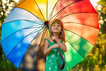 Happy child girl walk with multicolored umbrella under summer rain