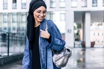 Stylish Muslim girl hijab stands among the city with a women's bag