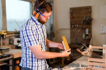 Bearded carpenter in goggles makes measurements hardwood timber for manufacturing of joiner's products