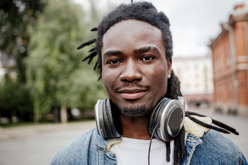 Portrait of an African man with headphones on a city street