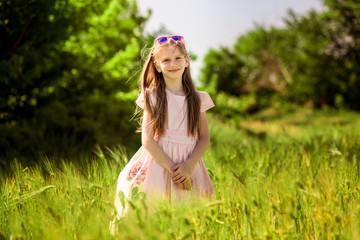 Portrait of adorable little girl in sunglasses in green summer field