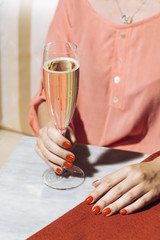 A glass of prosecco held by a girl in an elegant bar with vintage pop colors