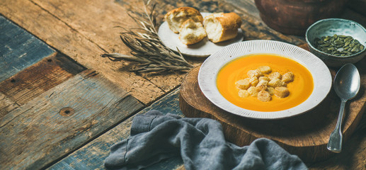 Fall warming pumpkin cream soup with croutons and seeds on board over rustic wooden background, copy space, wide composition. Autumn vegetarian, vegan, healthy comfort food concept