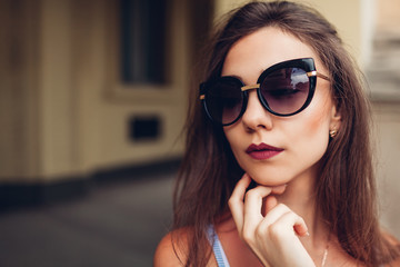 Outdoor portrait of young beautiful fashionable woman wearing stylish sunglasses. City fashion. Makeup
