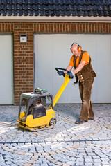 Workman compacting newly laid paving bricks.