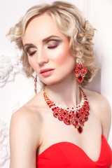Closed eyes. Young blonde model with curly hairstile and beautiful makeup and elegant gewelry, indoor, Studio shot