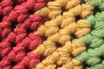 colorful background - macro photography of knitted wool structure in red, yellow and green