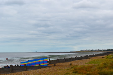 View of colourful windbreak on the sandy Herne Bay beach. Herne Bay, Kent, UK, August, 2018