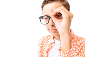 Young man looking through hand concept: looking into the distance or looking through binoculars, teen guy with glasses on white background in Studio Fotomurales