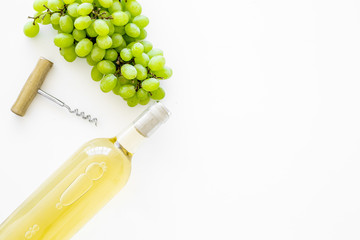 Fototapete - Open the wine concept. White wine in glass bottle near bunch of grapes and corkscrew on white background top view copy space