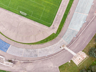 drone image of city stadium with soccer field and seats. aerial view from above
