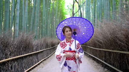 Wall Mural - Asian woman wearing japanese traditional kimono at Bamboo Forest in Kyoto, Japan.