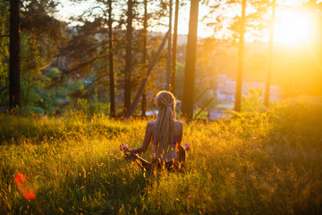 Silhouette of yoga woman on a picturesque glade in a green forest.