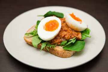 Healthy natural high protein snack whole grain toast with soft boiled egg, tuna and spinach