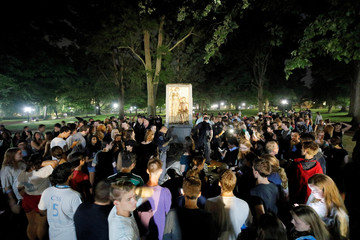 Students and protesters surround plinth where the toppled statue of a Confederate soldier nicknamed Silent Sam once stood, on the University of North Carolina campus after a demonstration for its removal in Chapel Hill