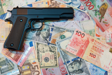 Black gun on various of international banknotes. illegal arms trafficking concept